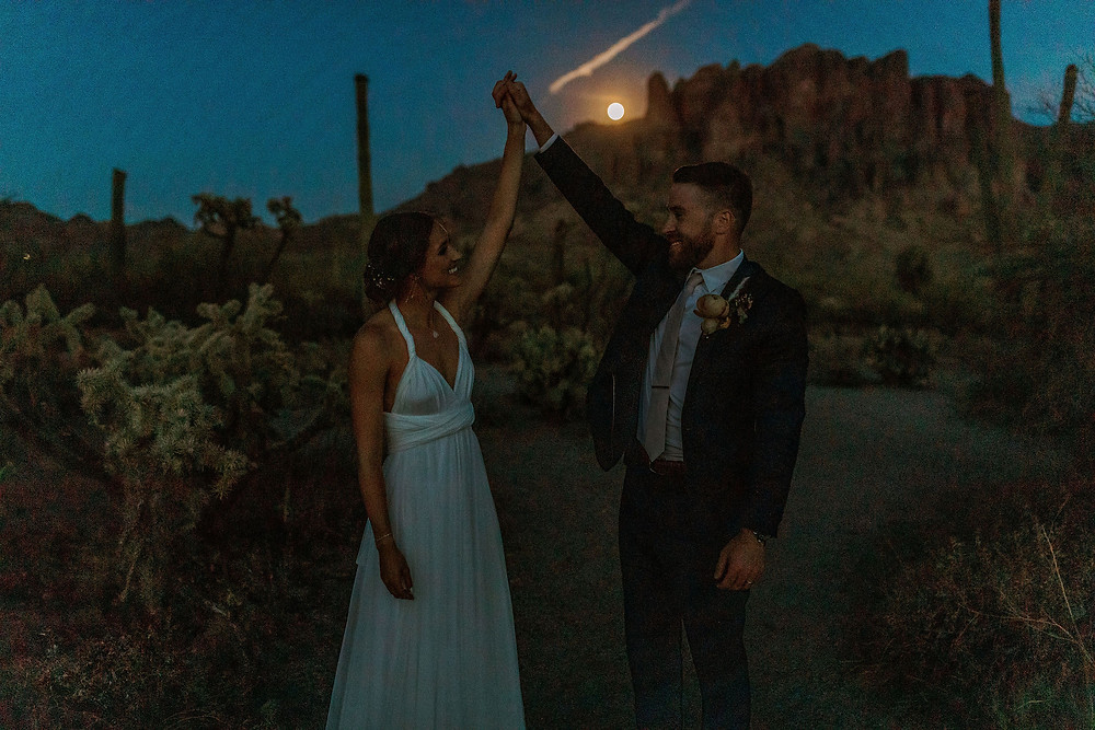 Bride and groom standing in the Arizona desert with a full moon and the Superstition Mountains in the background.