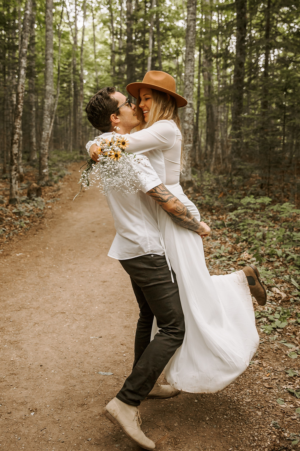 Bride and groom portraits after elopement in a Michigan forest trail holding a wildflower bouquet.