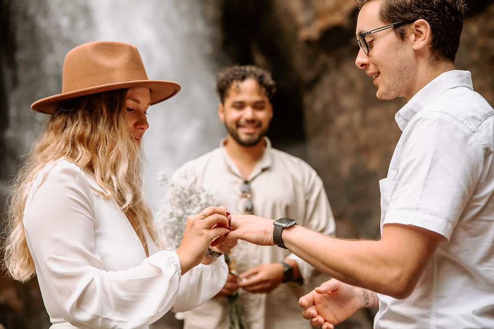 Bride wearing a brown hat and groom exchanging rings at their elopement.