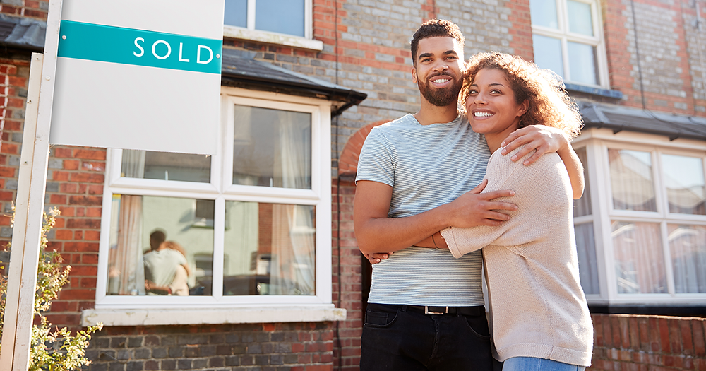 Can't sell your house? Here's what to do | Couple smiling outside sold house UK