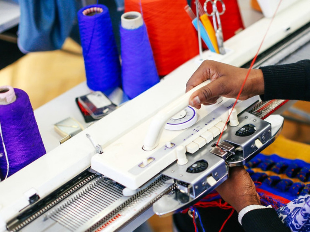 A person working on a knitting machine