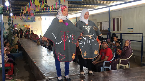Two girls wearing home-made ponchos reading LOVE SYRIA from the Zaatari Action project