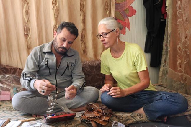 Helen and Tarek making jewellery in Tarek's Zaatari home – image by Yousef Alhariri