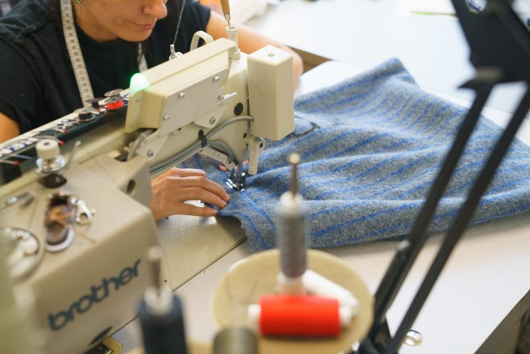 person repairing a piece of clothing on a sewing machine