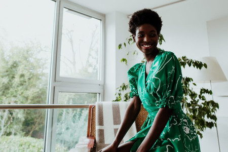woman sat in an apartment with plants wearing Birdsong dress