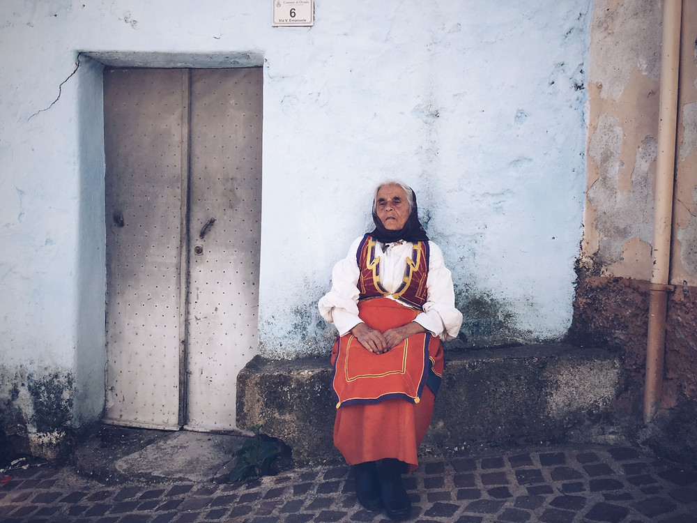 woman sat in a dress on the streets of Desulo