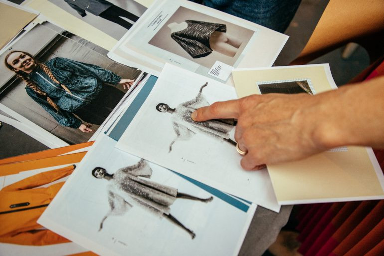 finger pointing at fashion design development drawings