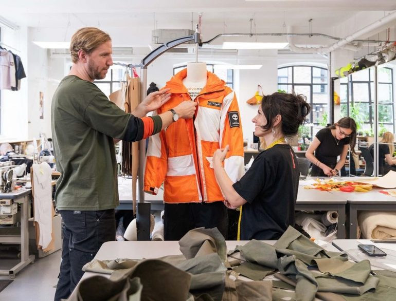 Christopher Raeburn in the studio working on a orange jacket with his team