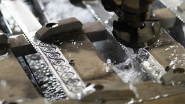 Buttons being cut out of knives through water jet. Photo by David Betteridge