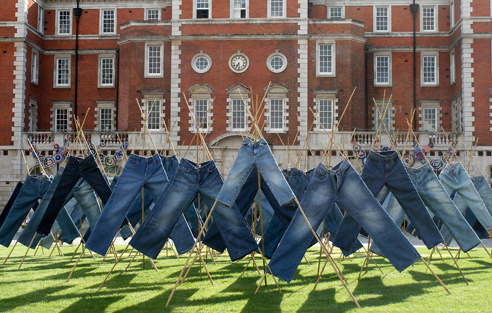 A series of catalytic jeans displayed on bamboo sticks outside Chelsea College of Arts