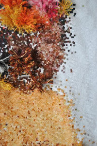 Close up embroidery of a black woman with floral headdress by Sara Marty