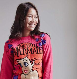 girl smiling wearing a little mermaid jumper