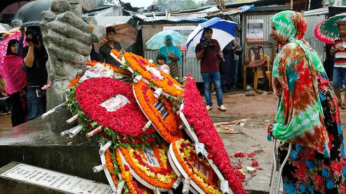 woman mourning stood alongside flower in bangladesh