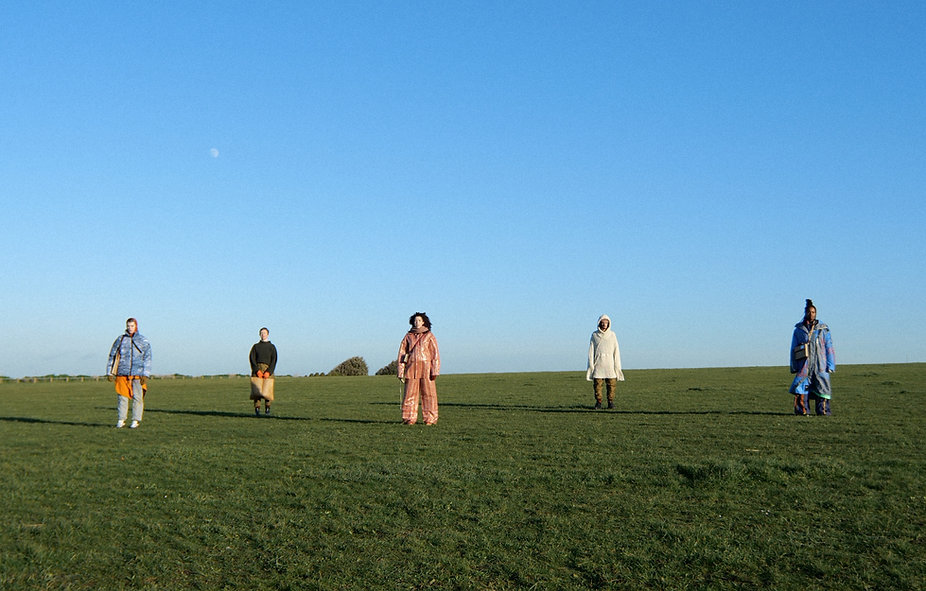 A landscape image of five people standin