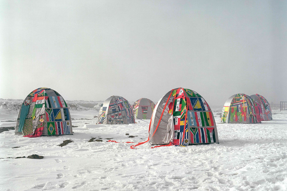 Multicoloured flag covered tents in antarctica in the snow