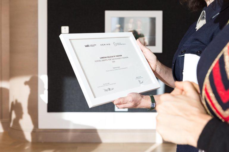hands holding a Kering Award certificate