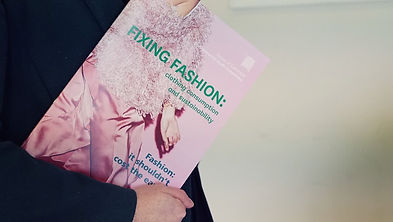 Person holding booklet that reads 'fixing fashion'
