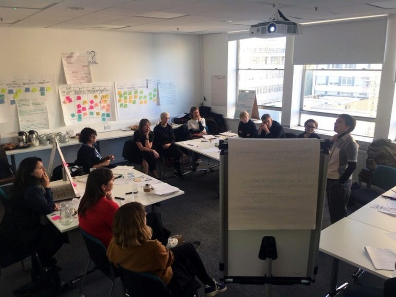 A FashionSEEDS workshop in action multiple people looking toward a flipchart