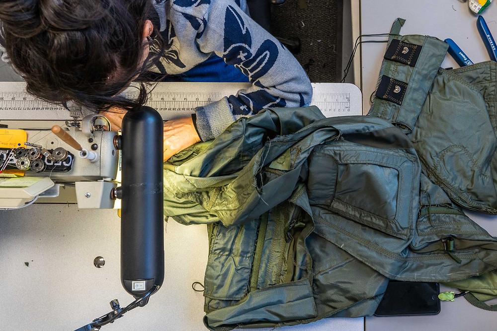 Woman working on a sewing machine making a Raeburn jacket.