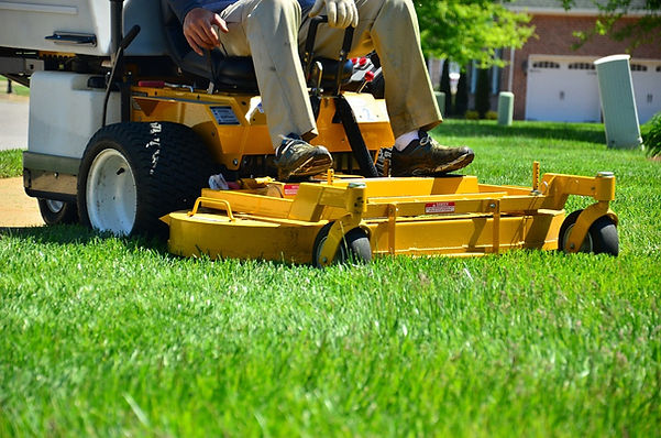 Yard worker sitting on commercial zero turn mower cutting grass