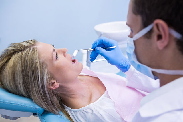 dentist-examining-woman-at-clinic-J8VFC9