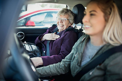 Photo of younger woman driving older woman