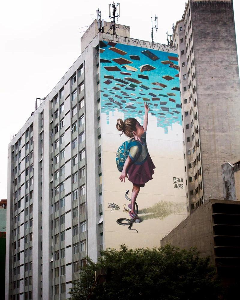 Menina pegando livros no ceu, grafite em empena cega de Apollo Torres