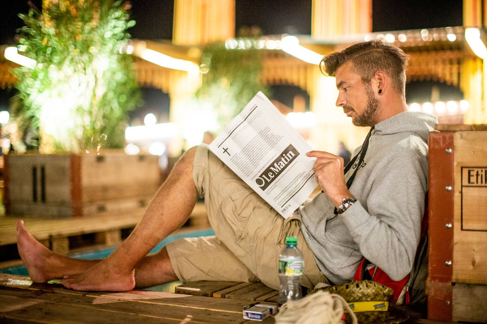 A young man reading last paper edition of newspaper Le Matin