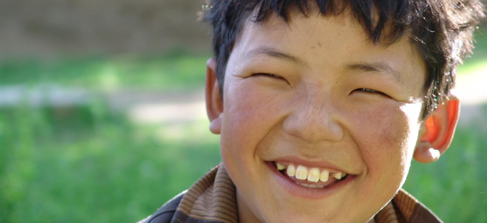 A Tibetan boy smiling.