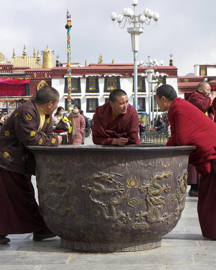 Monks relaxing in Barkhor Square.JPG
