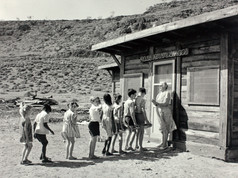 It's time to line up and head back into the classroom this week for Territory school kids. Here, Mrs Newbold greets her full compliment of students of Ross River School, about 80 kilometres west of Alice Springs in 1965. On Arrernte country, but run as a pastoral lease from 1896, the school mostly serviced the little ones of Loves Creek Station. From all accounts, the classroom which was also known as 'cabin 13', was a little spooky, too spooky in fact for local tourists to stay in, so instead became the schoolroom. Former students recall some sort of portrait above the fireplace with eyes that seemed to follow you around the room.  21 July 2019  Image: Robin Smith Collection, Northern Territory Library
