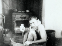 """With weather records being smashed throughout Central Australia this week, you've got to take a leaf out of this bloke's book and get cool any way you can. Pictured here are the bath facilities for the local policeman in Tennant Creek in the 1950s, a position filled by Constable Bob Savage, who oversaw a great crime wave of disorderly behaviour and drunkenness of 1952, when this photo was taken. But keeping cool and clean came at significant cost. He wrote on the back of the photo that """"Tennant Creek water costs 5 shillings per 100 gallons"""".  17 March 2019   Image: Savage Collection, Northern Territory Library"""