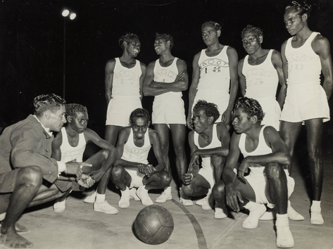 "The Bagot ""All Black"" Basketball team. They formed in 1953, just five years after the newly established NT Basketball Association held its first competition in Darwin and quickly became ""all the rage"", according to the papers at the time. Ahead of their first season, the Bagot team was reportedly ""wearing out balls in practice matches at the rate of about one every ten days"". Their games held at a boxing stadium in Cavenagh Street drew big crowds, many of whom came to see the talents of defence Jack White (squatting third from the left), who was known for his speed and ""coolness under pressure"". The team even funded equipment by repeat performances of a corroboree performed to the Queen and Duke on their 1954 tour. An exhibition celebrating 70 years of basketball is now on at Northern Territory Library until 26 May, developed with basketball legend Maisie Austin.  14 April 2019  Image: Harney McCaffery Collection, Northern Territory Library"