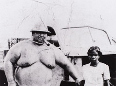 Meet the man who once claimed to be the Territory's largest and strongest. A former sideshow strong man and miner, Charles 'Tiny' Swanson moved to the NT and ran a market garden at Maranboy near Katherine in the 1940s and 50s, with wife Ruby (pictured) and her pet wallaby. Weighing 240 kilograms, his strength was the stuff of legend. He could apparently load 44-gallon fuel drums onto a truck by himself, and was said to have once lifted the end of a 22-foot piece of railway line while seven other men struggled with the other end. He fell ill in 1954 and when he died shortly after, a two-tonne crane was required to lower his oversize coffin at what is now the Gardens Cemetery.   6 January 2019  Image: Eric Martin Collection, Northern Territory Library
