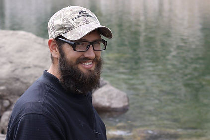 Picture of a bearded man in a camo hat and black shirt near a lake