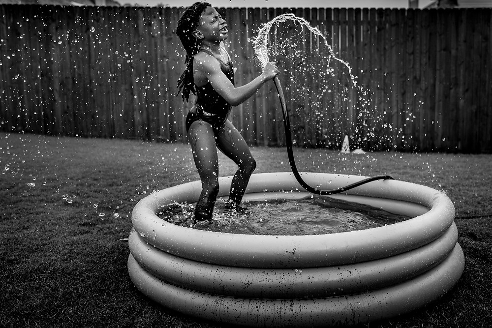 girl playing with water hose in the backyard