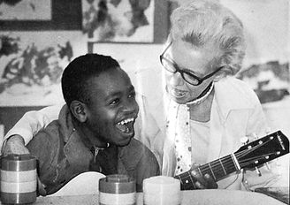 Older white woman singing with young black boy who has disabilities.