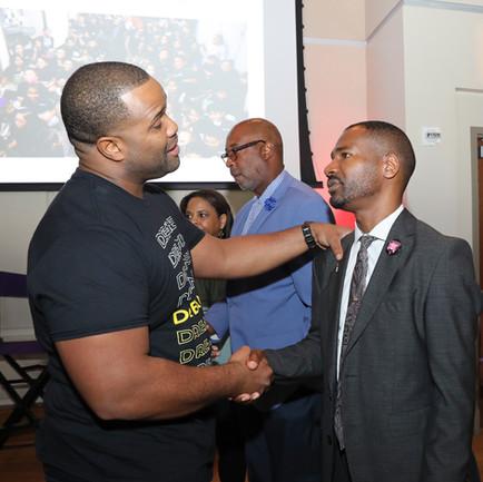 Kev Marcus of Black Violin speaking with the Principal of Walker Elementary School