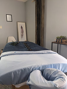 Spa Room at The Deep Tissue Spa, hot stones are laid attractively on a massage table with a eucalyptus branch, a small table is visible with three aromatherapy oils ready to be used, a painting of a feather hangs on the wall and a fiber art installation hangs dreamily on the opposite wall