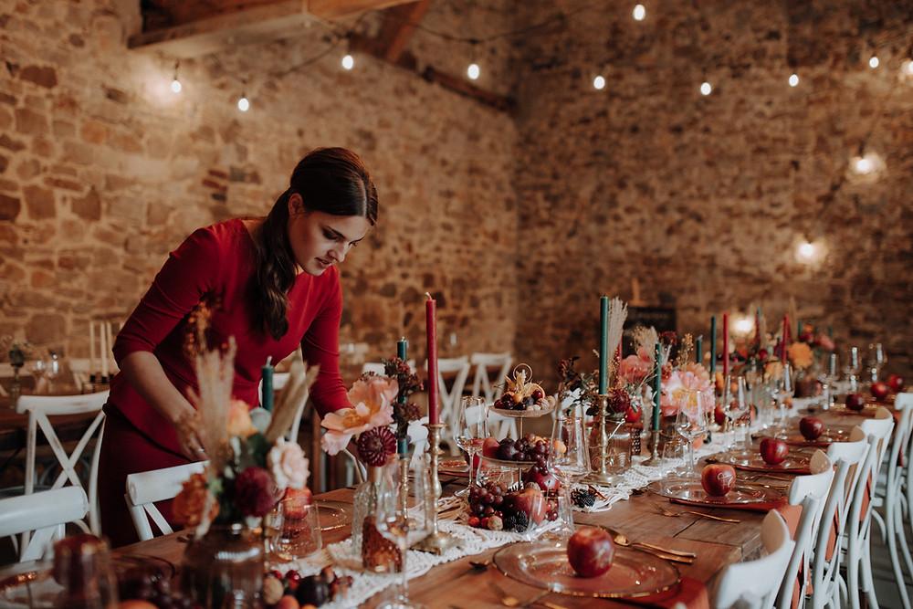 Eine Hochzeitsplanerin bei den letzten Handgriffen an der gedeckten Tafel