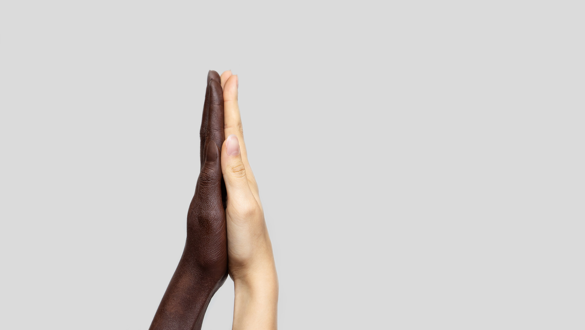 Black-and-white human hands touch palms