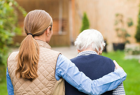 Young carer walking with the elderly wom
