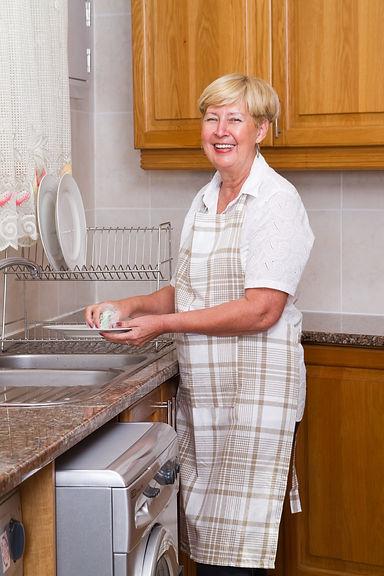 happy senior woman washing dishes in kit