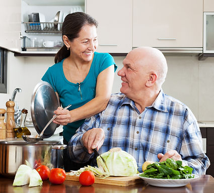happy mature  couple cooking vegetarian