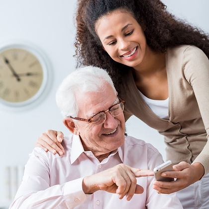 Young carer showing elderly happy man ho