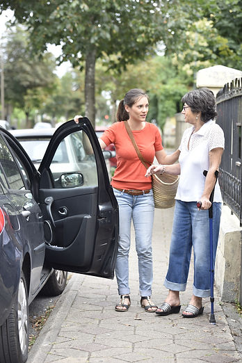 Young carer helping senior woman getting