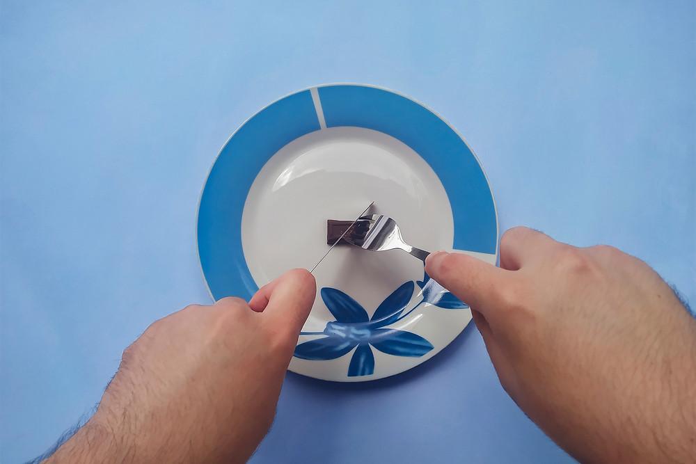 Fundo azul. Duas mãos usam talheres de prata para cortar um pequeno tablete de chocolate sobre um prato de porcelana branco com detalhes azuis