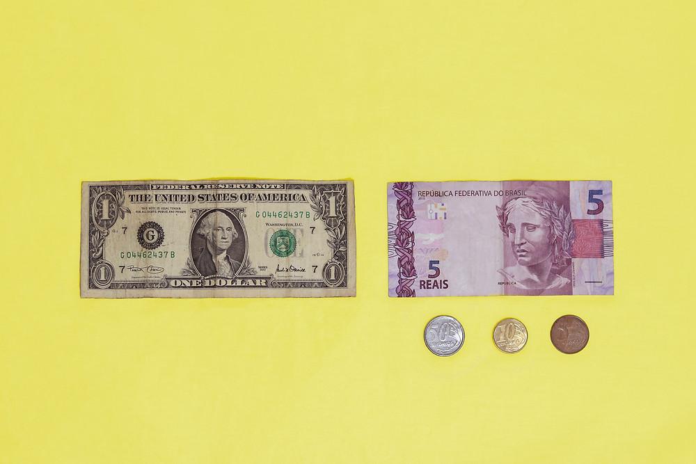 Fundo amarelo. Comparação lado a lado entre uma nota de um dólar e o seu valor aproximado em reais: cinco reais e sessenta e cinco centavos