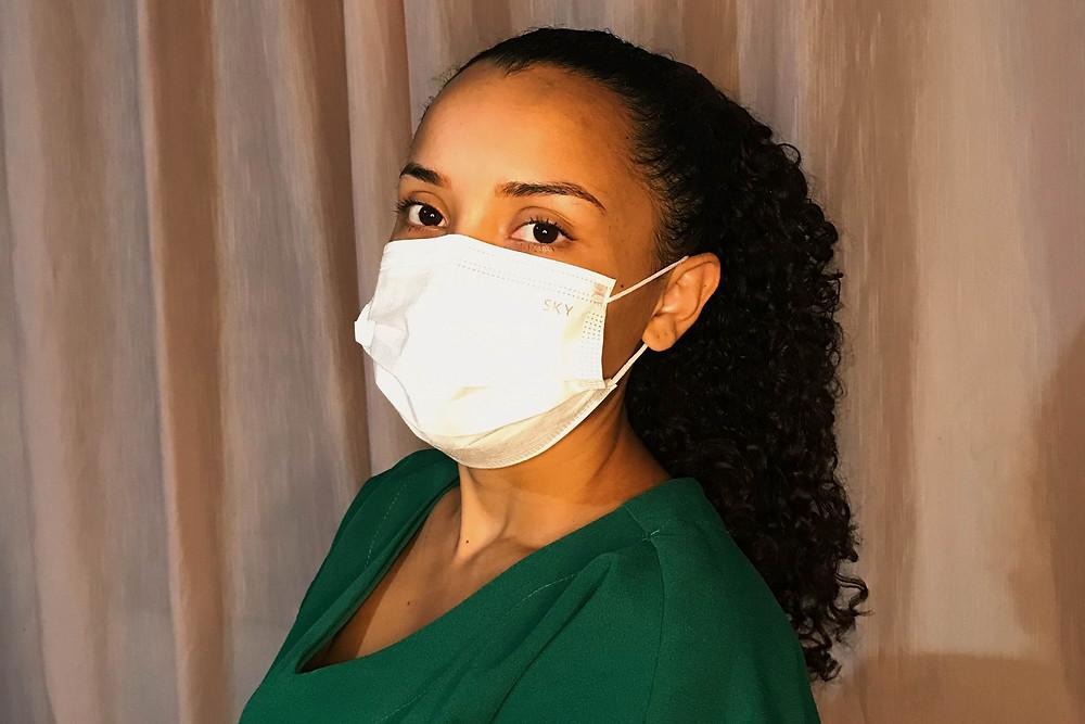 Karliany veste roupa verde de técnica de enfermagem e usa mascára. O seu olhar penetrante para câmera se destaca pelo brilho de seus olhos