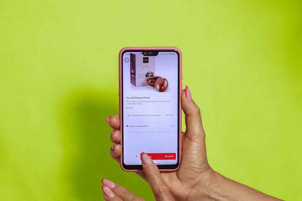 Fundo verde. Na imagem uma mão segura um celular no qual se vê uma página do Ifood vendendo um Ovo de Páscoa de trezentos gramas por quase setenta reais